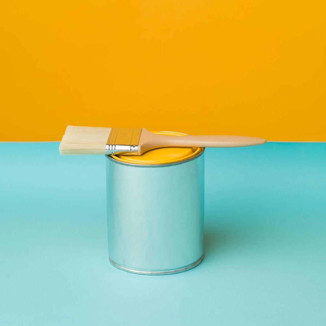 Färgburk och pensel i turkost samt senapsgul.