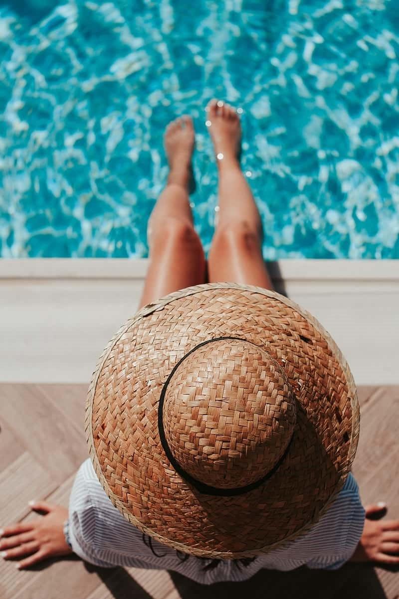 Kvinna sitter på poolkanten med fötterna i vattnet.