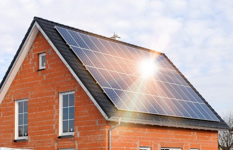 Tegelhus med solpaneler på taksidan som vetter mot söder.