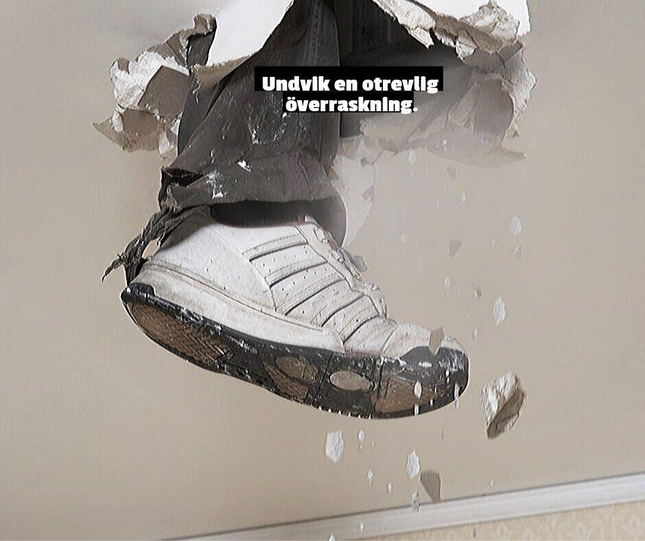 Man trampar ena foten genom golvet på ovanvåningen i ett hus.