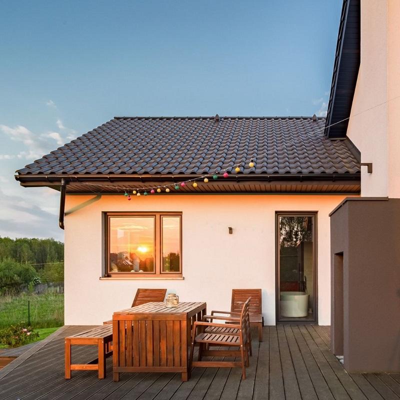 En stor altan som sitter ihop med ett vitt hus.