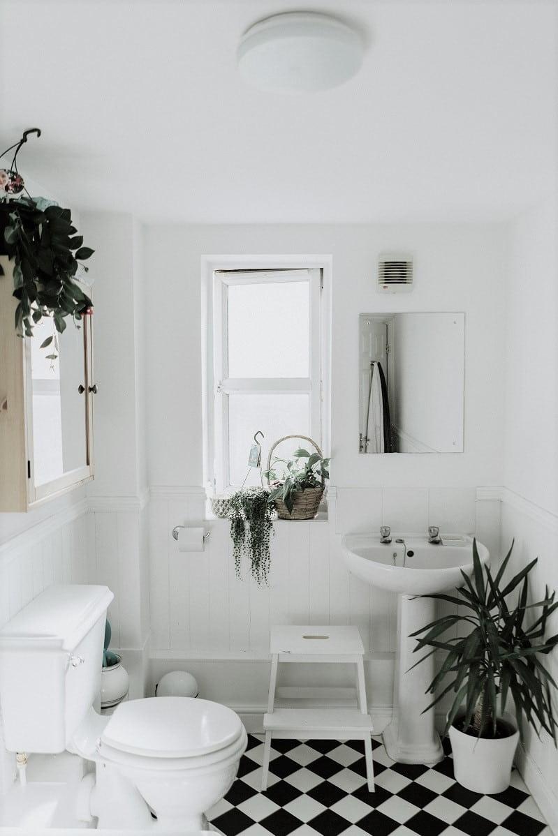 Badrum inrett med mycket gröna växter, vita väggar och schackrutigt golv.