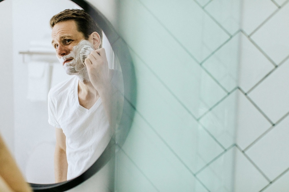 Man rakar sig. Han speglar sig i en rund badrumsspegel.