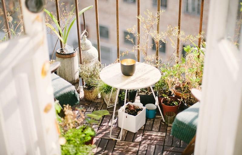 Balkong inredd med gröna växter, ett runt bord och fåtöljer.