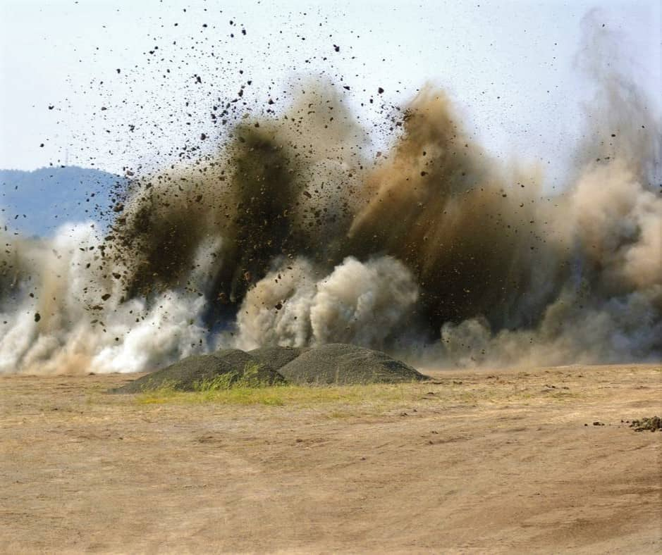 En markfirma spränger berg så att marken sedan går att schakta.
