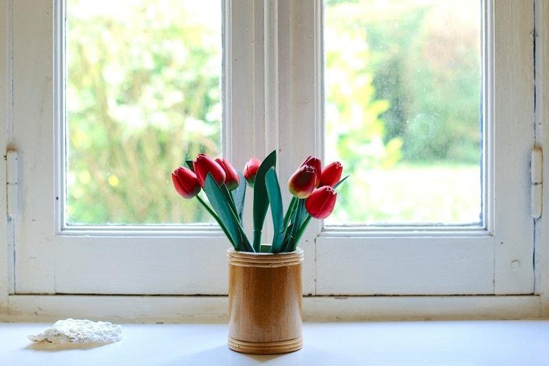 En vas med tulpaner framför ett vitt fönster.