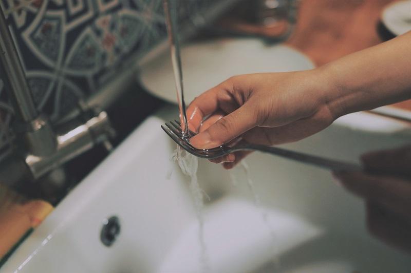 En tjej diskar en gaffel och vattnet rinner ner i avloppet.