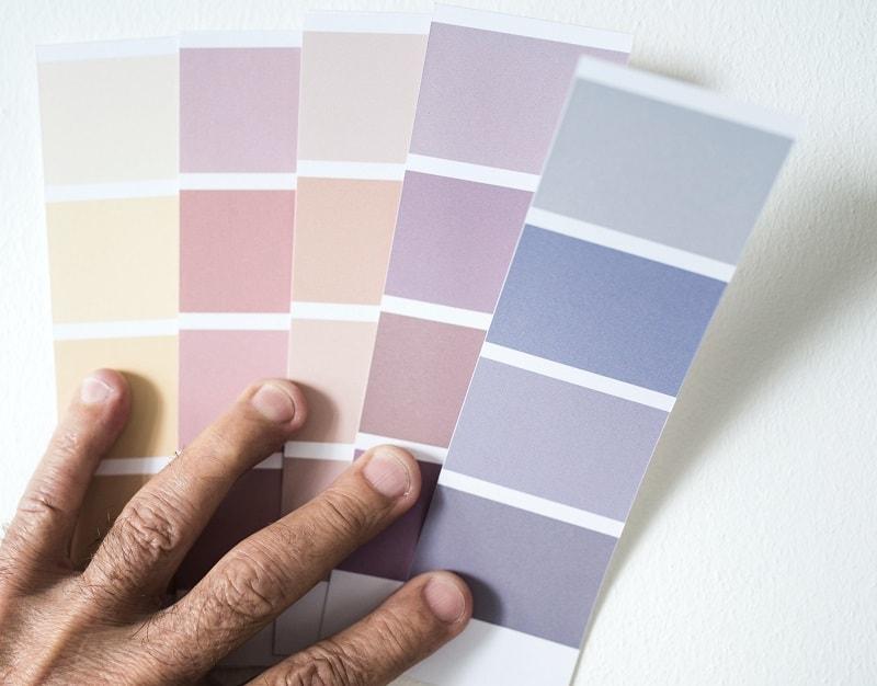 En man håller upp en färgkarta mot väggen.