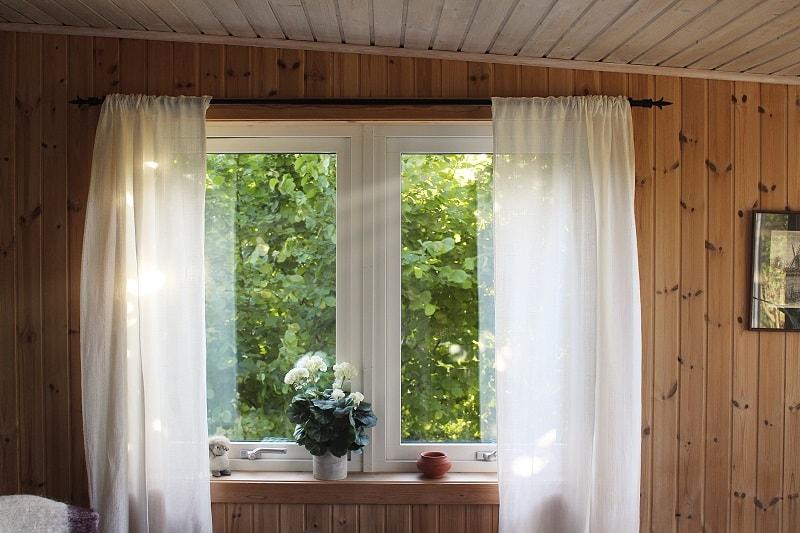 Ett stort fönster med vita gardiner.