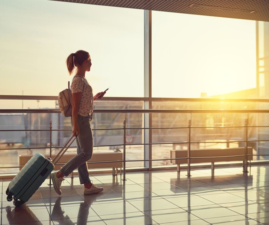 Kvinna går igenom terminal med en rullväska, på väg att åka utomlands.