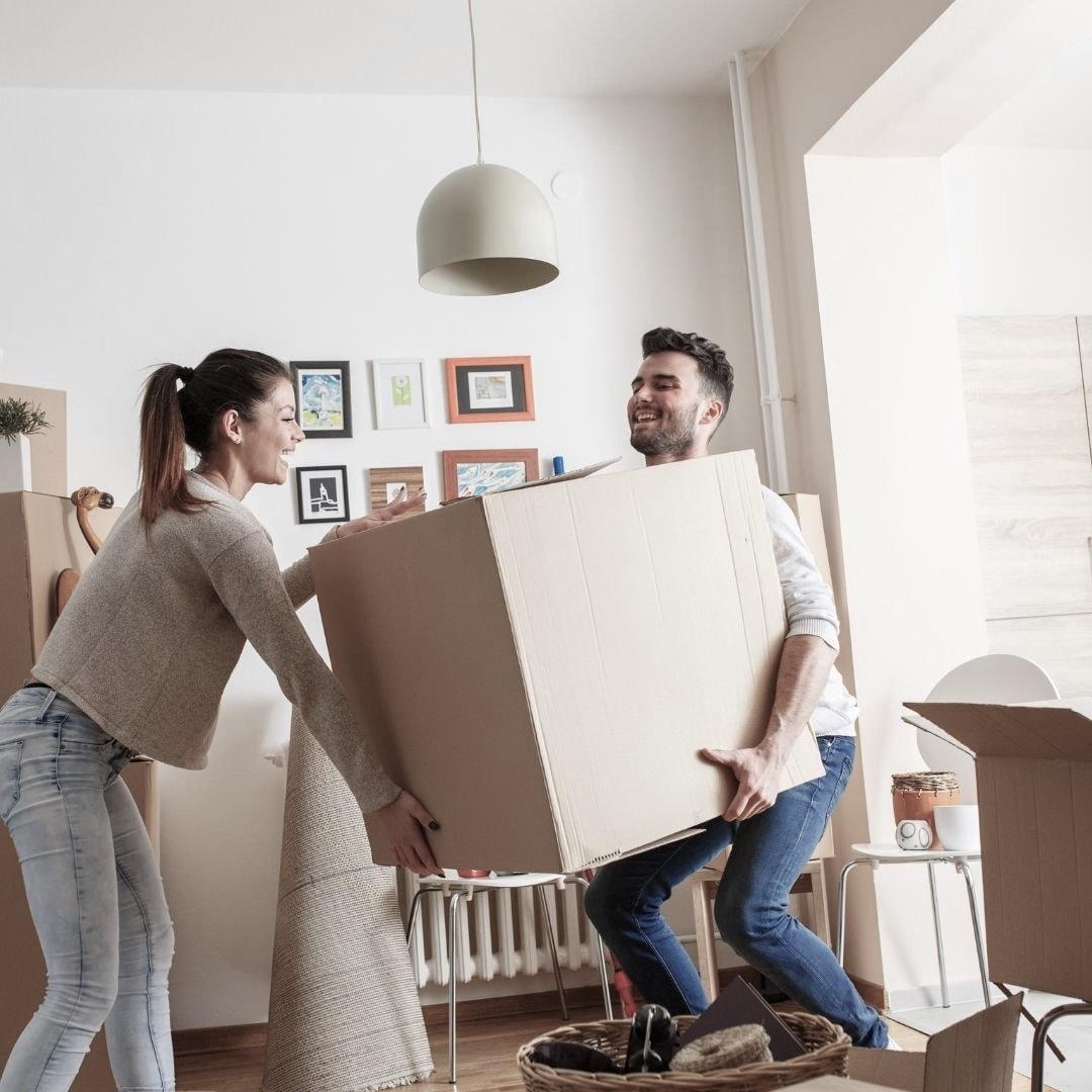Ett par hjälps åt att lyfta en flyttkartong som de har packat.