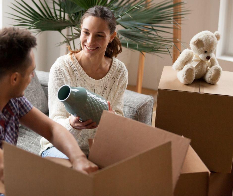 En man och en kvinna packar ner saker i flyttlådor.