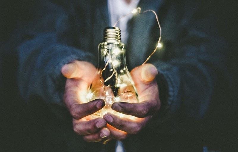 Man håller en glödlampa i händerna.