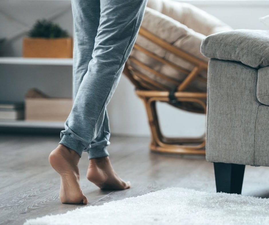 Person går barfota över golv som värms upp med hjälp av golvvärme.