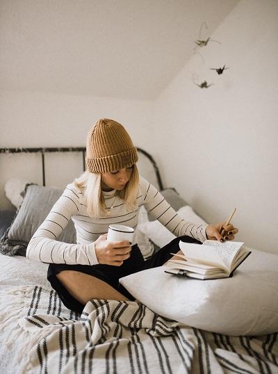Kvinna sitter i säng med mössa på huvudet. Hon skriver i anteckningsbok.