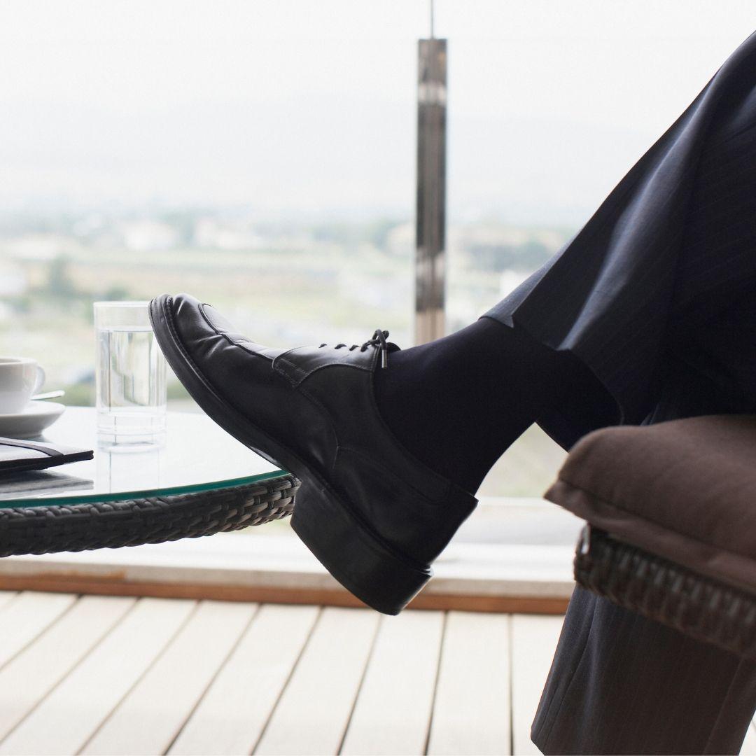 En man dricker kaffe på en inglasad balkong.