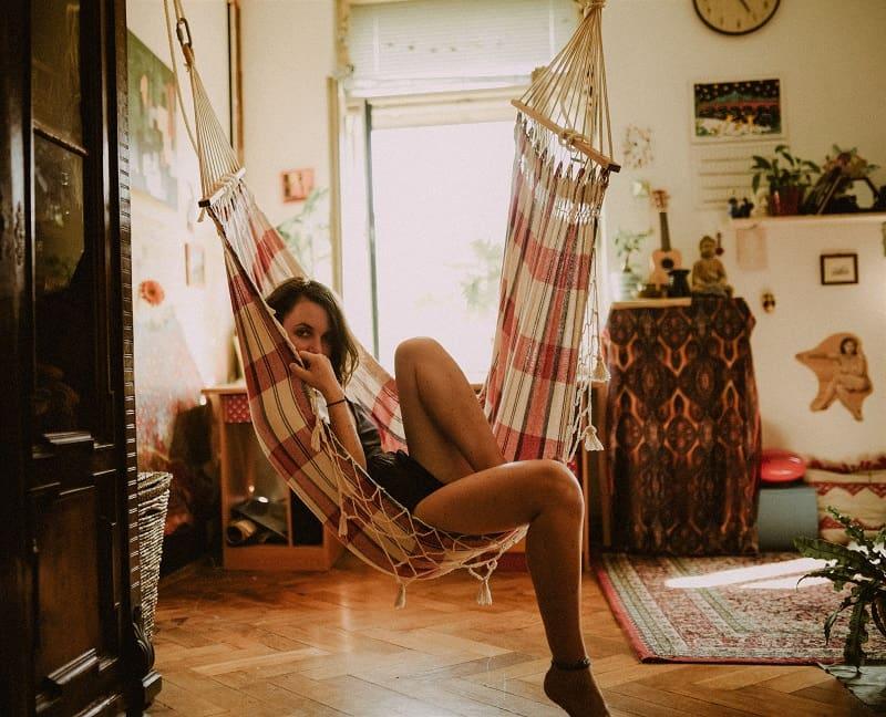 Kvinna sitter i en hängmatta som hon har monterat upp i sin lägenhet.