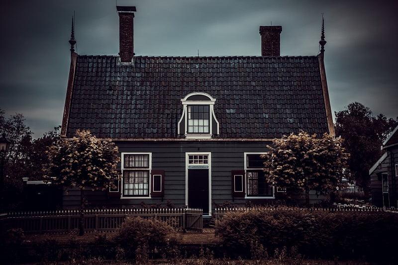 En villa mörk villa med dramatiskt lutande tak och svarta takpannor.