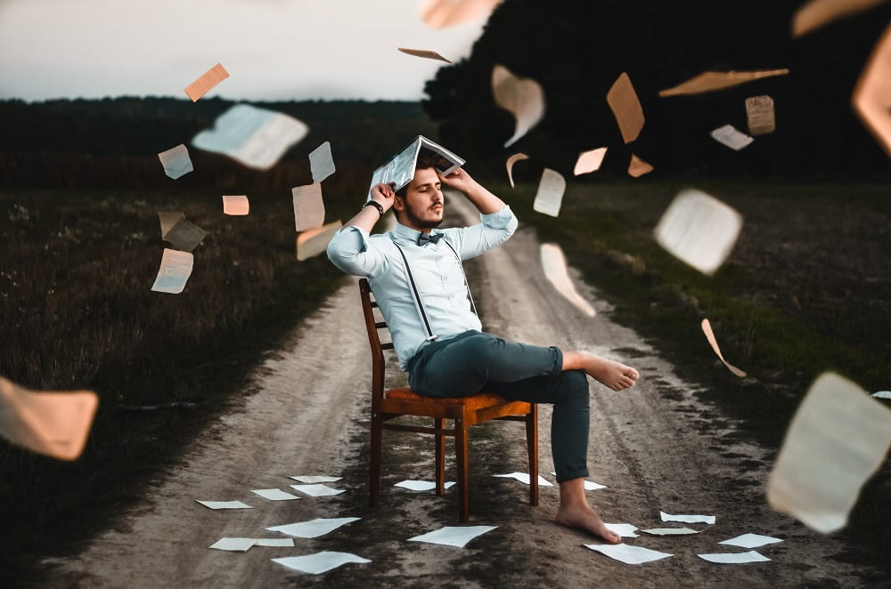 En man sitter på en stol med en bok över huvudet. Det flyger bokblad runt honom. Han har mycket att hålla reda på.