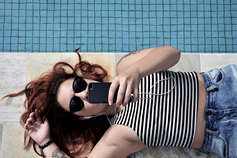 Kvinna ligger på poolkanten och surfar på mobilen.