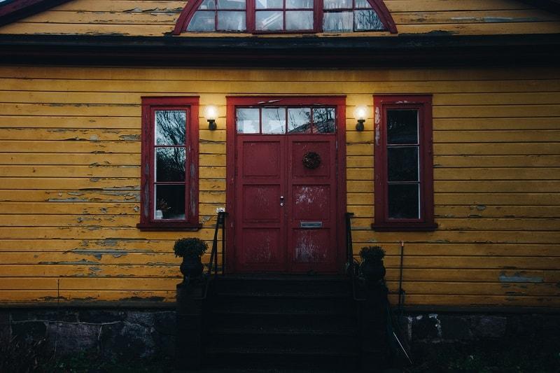 Ett gult hus som är i behov av att renoveras.