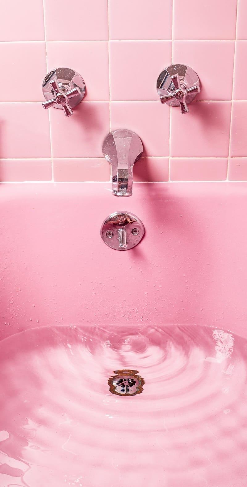 Ett badrum som är renoverat med rosa kakel och rosa badkar.