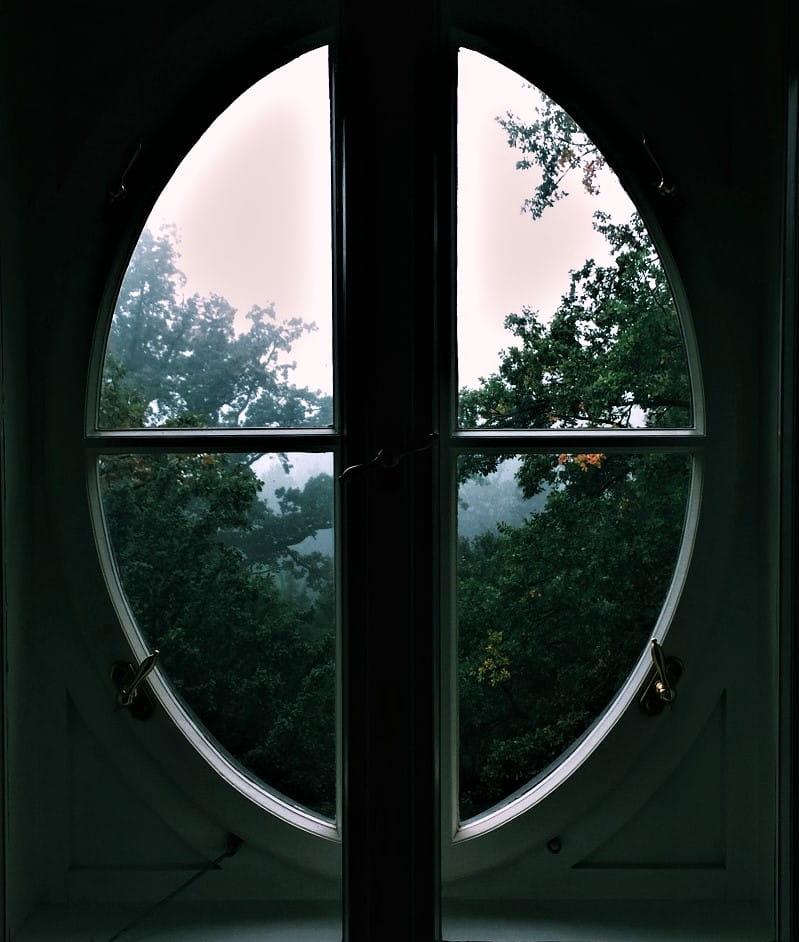 Ett runt fönster med utsikt mot grönska.