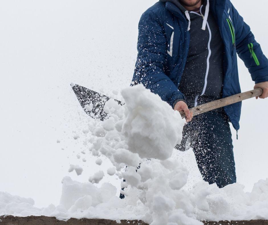 Man skottar snö från tak.