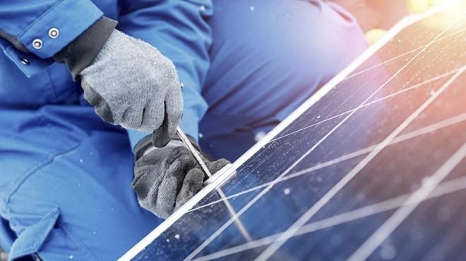 Soleltekniker installerar solceller på tak.