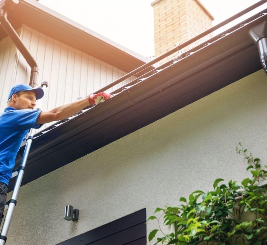 En takläggare inspekterar taket på en villa.