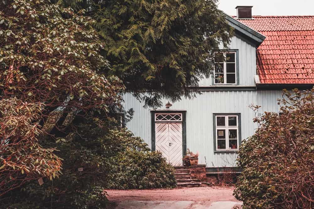 Ett hus som sticker fram bakom några buskar och träd