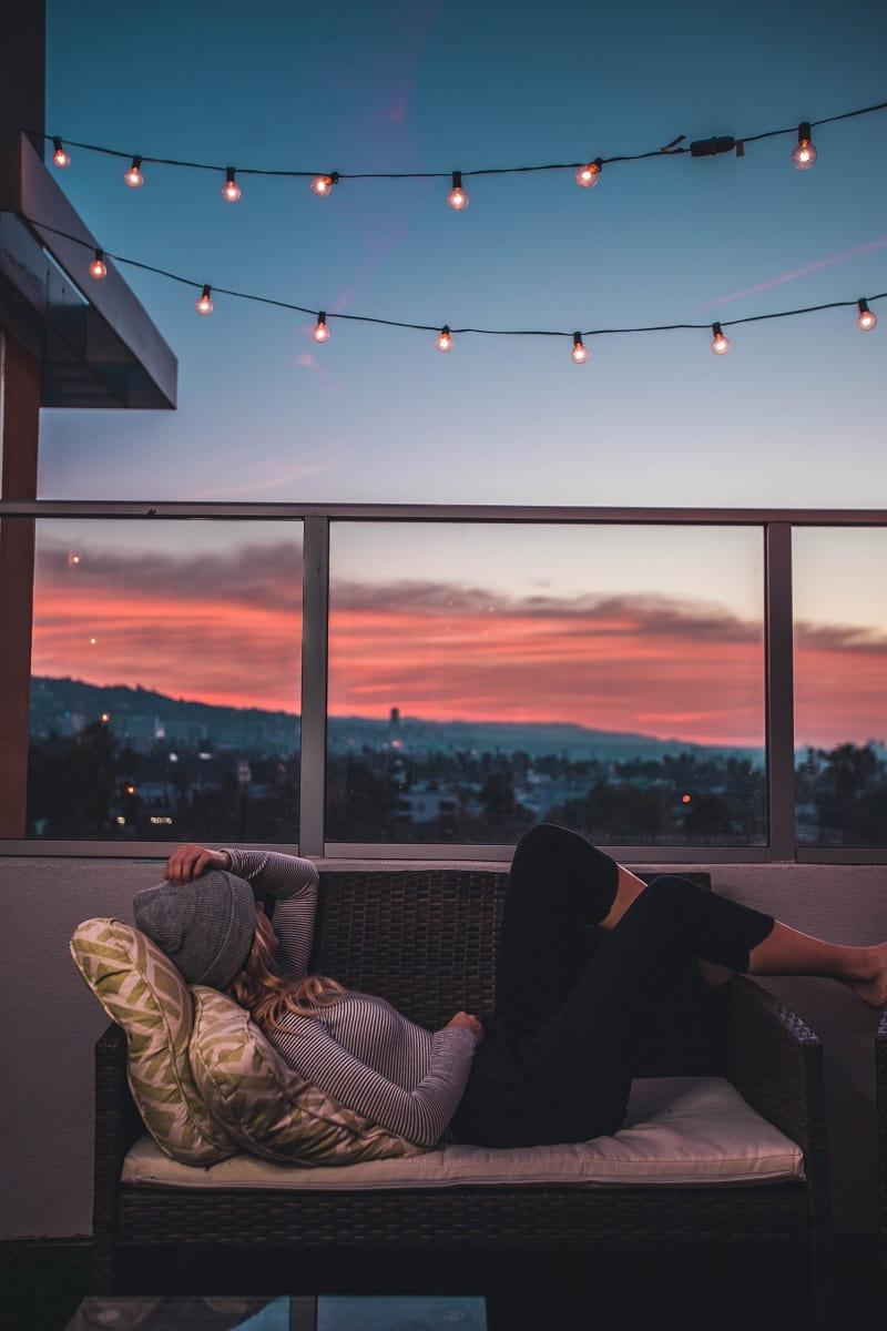 En balkong med en skön soffa där man kan slappa och njuta av kvällssolen.