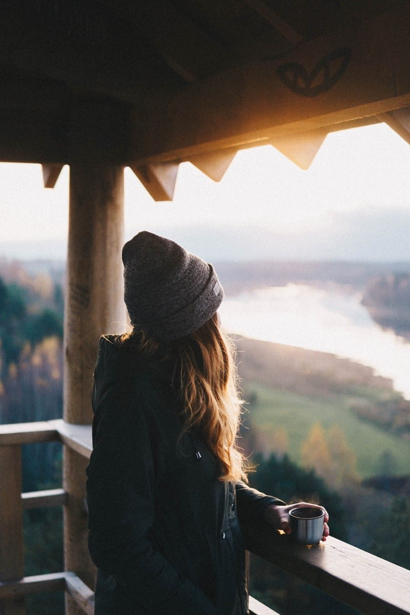 Kvinna står utomhus och blickar ut över landskapet. Hon värmer upp sig med en kopp kaffe.