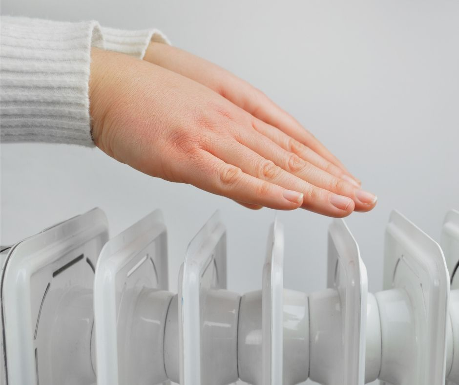 En tjej håller händerna ovanför ett element.